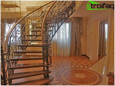Stairs from the framed by openwork forged fence of dark wood gives the interior a special solemnity