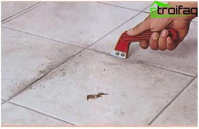 Removing grout from the tile floor with a scraper