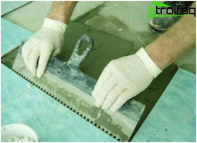 Leveling the adhesive with a notched trowel