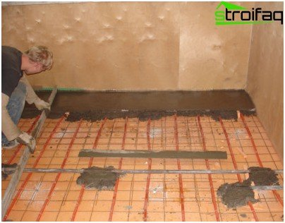 Pouring concrete mixture over the layer of mineral wool and a reinforcing grid