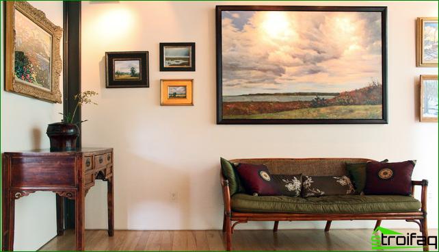 Panel med målningar av olika storlekar på hallväggen