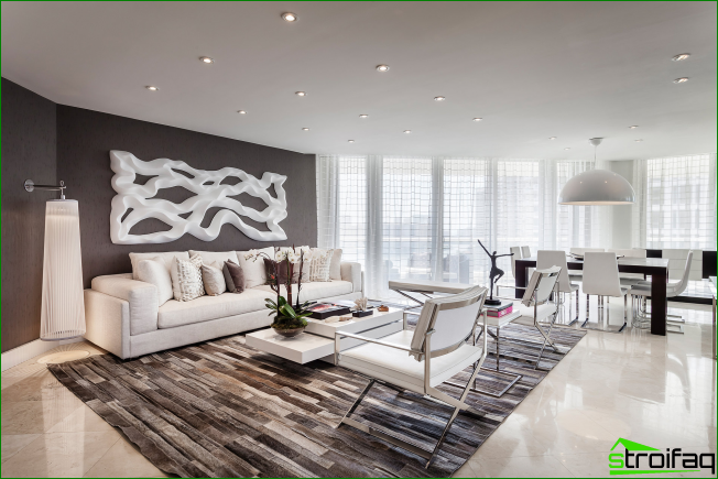 A large studio room spacious apartment in gray tones. Spotlight - a large volumetric abstraction on the wall above the sofa, which supports the overall mood of the room