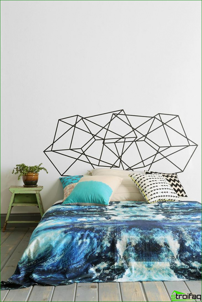 Large bright bedroom with unusual geometric pattern over the headboard and a bright accent in the bedding with marine motifs