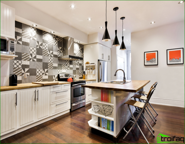 The original kitchen apron with graphic ornaments complement the interior of bright kitchen-studio
