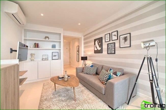 Horizontal stripes on the wallpaper of one of the walls of the living room visually increase the space