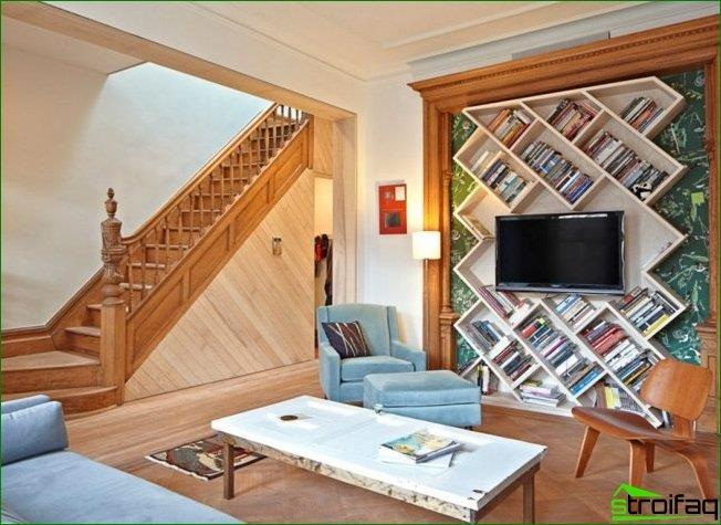 Design solution for a country house living room: TV shelf is placed in the cut with diagonal shelves for books
