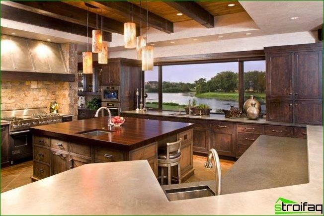 Luxury kitchen with wooden kitchen unit and a panoramic window on the wall, decorated windowsill, countertop
