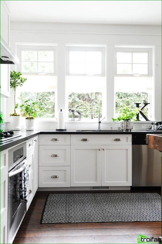 Bright kitchen with a window sill, countertop simulating natural black marble