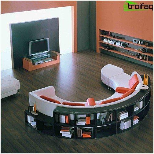 En sofa med hylder integreret bagpå ryglænet forbedrer akustikken i hjemmebiografområdet i stuen markant
