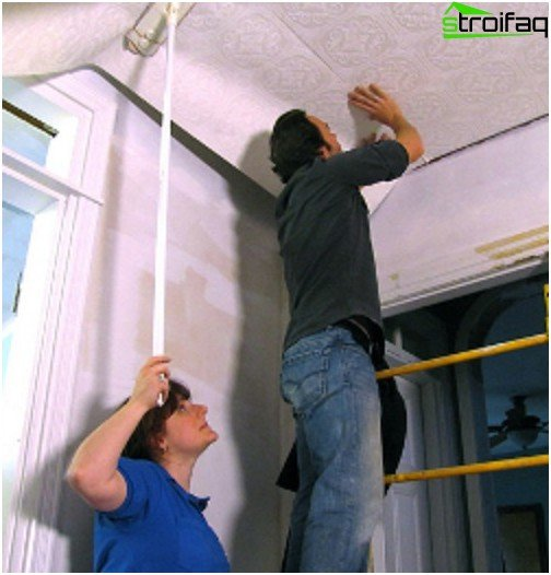 Gluing ceiling wallpaper with an assistant