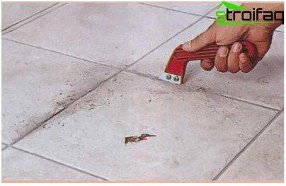Grout van vloertegels verwijderen met een schraper