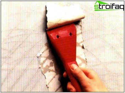 Eliminamos el papel tapiz después de humedecerlo y perforarlo.