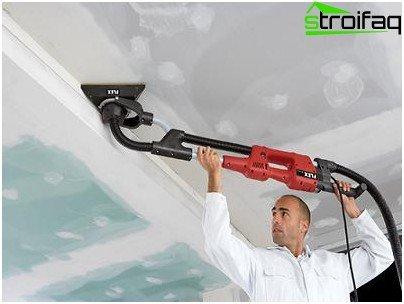 Het plafond schuren met een slijpmachine