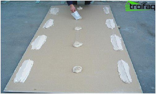 تطبيق الغراء على الحوائط الجافة أثناء تسوية الجدران
