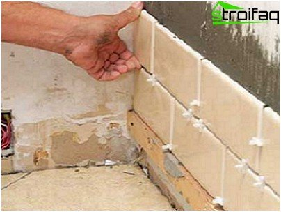 The process of laying tiles on the wall