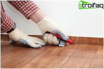 Wir schneiden das Linoleum auf den Fußleisten