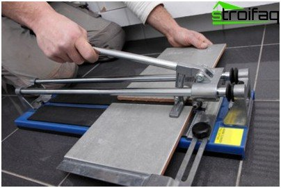 Sawing tiles with a manual tile cutter