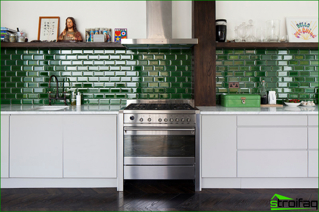 Kiiltävä kaakeloitu keittiön esiliina koristaa valoisaa keittiötä