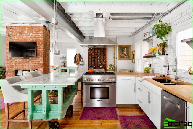 Tilava valoisa keittiö, jossa on kirkkaat sisustuselementit ilman yläkaappeja