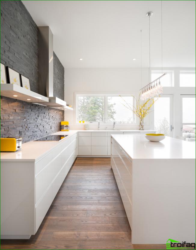Minimalistinen valkoinen keittiö ilman yläkaappeja, joissa tumma koristekivi yhdellä seinällä