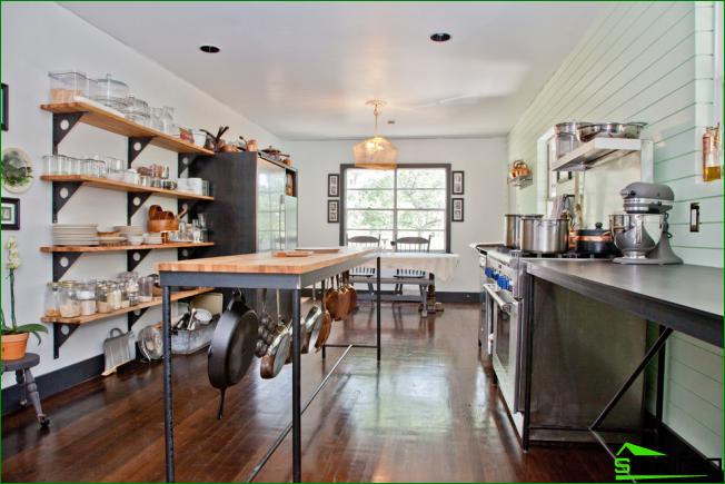 Keittiön pöydän alla on runsaasti hyllyjä ja koukkuja, jotka korvaavat tilavat yläkaapit