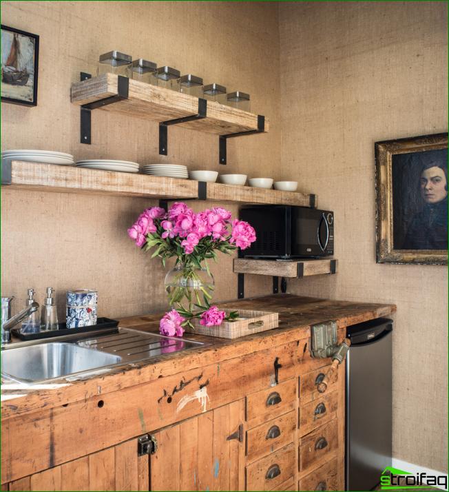 Tyylikäs maalaistyylinen keittiö, joka on sisustettu pienillä maalauksilla