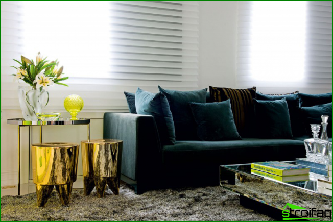 The luxurious combination of a velvet sofa with gold stools and an almost imperceptible mirror coffee table