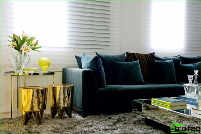 La lujosa combinación de un sofá de terciopelo con taburetes dorados y una mesa de café con espejo casi imperceptible