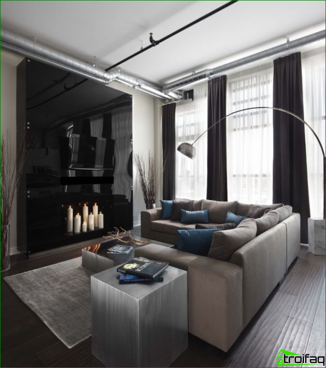 Black glossy wall equipped with a fireplace made of candles and as the basis for TV