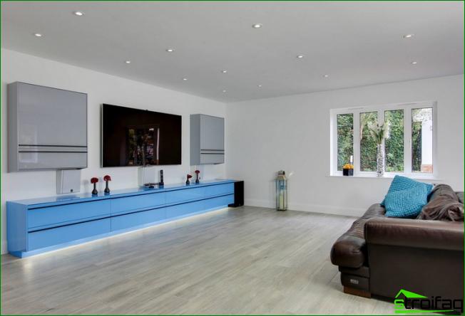 Amplia sala de estar con muebles brillantes en colores fríos.
