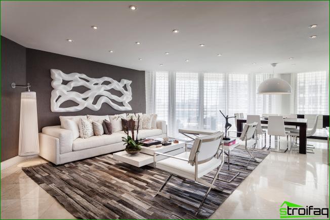 Amplio estudio en un amplio apartamento en tonos grises. El foco de atención es una gran abstracción voluminosa en la pared sobre el sofá que mantiene el ambiente general de la habitación.