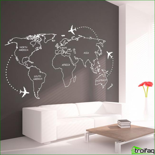 Sala de estar minimalista con gráficos originales en una pared gris oscuro junto al sofá. Tenga en cuenta que un pequeño énfasis en los colores rojos puede diluir el interior monocromático.