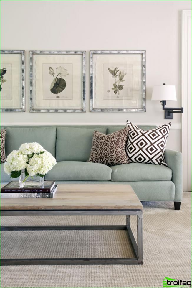 Una pequeña sala de estar en colores pastel con elementos gráficos en las fundas de almohadas y dibujos delicados como parte de