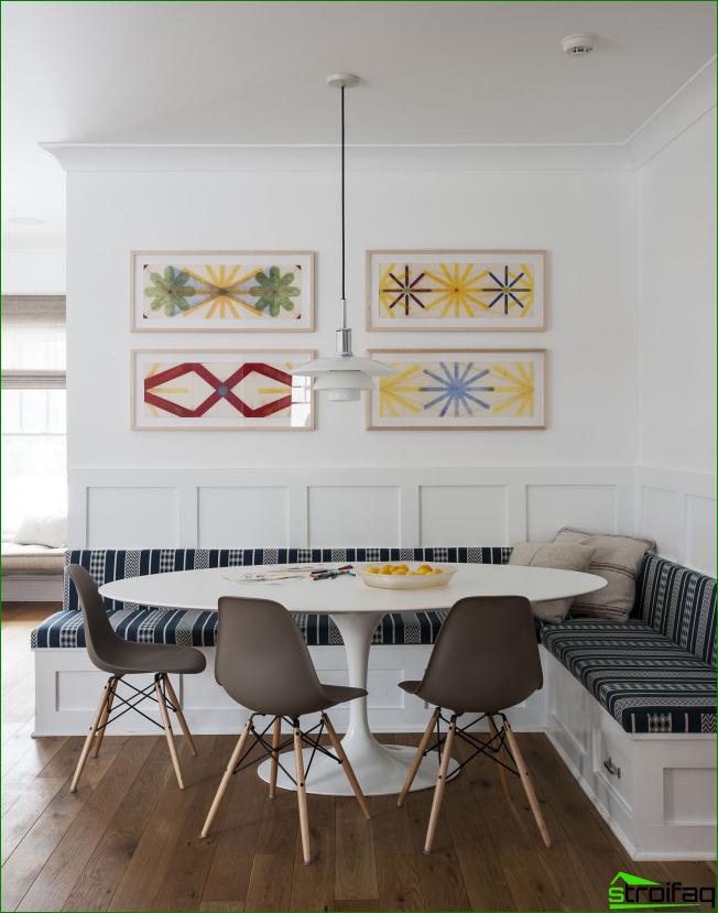 Área de comedor del estudio de la cocina en colores brillantes con adornos gráficos en las esquinas cubiertas otomanas