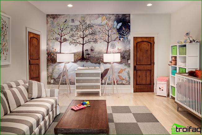 Parte de la pared en la habitación de los niños está pegada con papel tapiz fotográfico. Hay una variante de paneles modulares que se pegan a la pared y crean