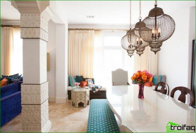 منطقة لتناول الطعام على الطراز المغربي: مفصولة عن غرفة المعيشة بفتحة مقوسة. تستخدم الأضواء التقليدية ومزهرية من الزهور كديكور