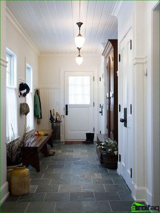 Hallway in the Provence arc: a wooden bench, an umbrella stand and an open hanger instead of traditional wardrobes