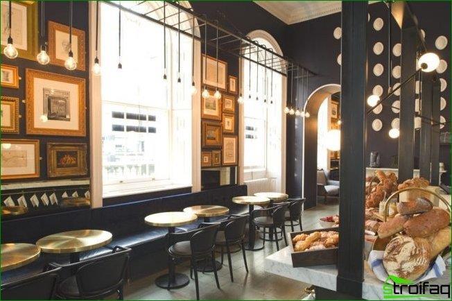 Hermoso interior moderno con paredes negras y pequeños cuadros en marcos dorados.