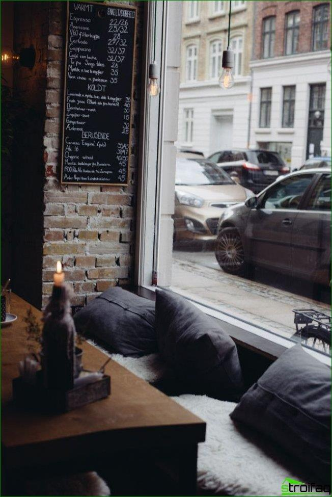 Las almohadas suaves junto a la ventana y la pared de ladrillo son una buena opción para decorar una pequeña cafetería en estilo loft.