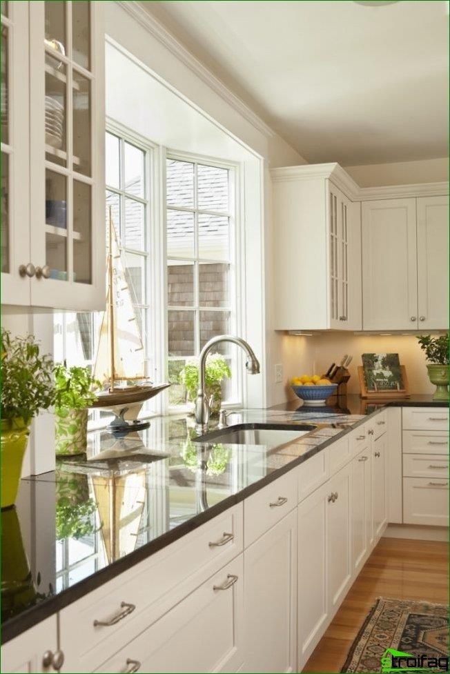 The kitchen of a private house with a non-standard, protruding outward window frame, which allows you to increase the area of the working surface of the window sill-countertops