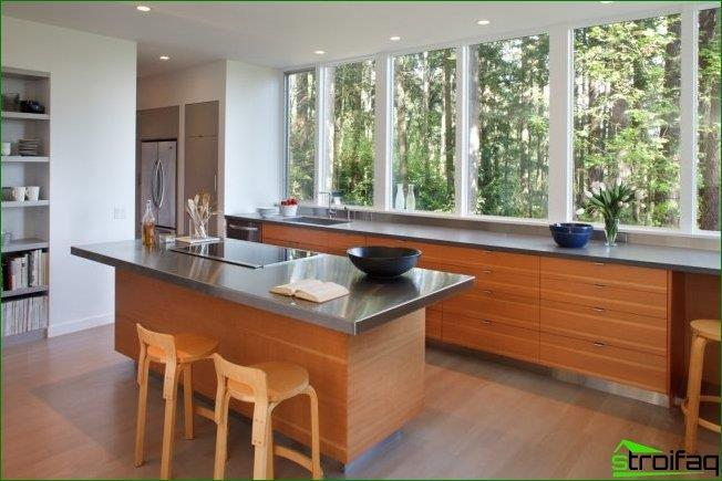 Spacious kitchen with a large panoramic window on almost the entire wall. The window sill looks very organic in this design of space