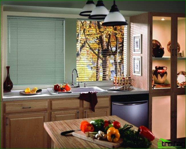 A small kitchen in pastel colors with a wooden kitchen set and a very practical tabletop window sill
