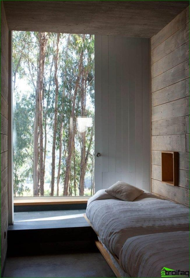 A cozy bedroom in a private house with a low window-sill, which perfectly replaces the bedside table